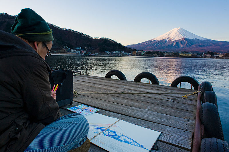 An_elderly_Japanese_man_sittiong_on_a_small_wooden_pier_drawing_Mount_Fuji_as_seen_at_sunrise_across_lake_Kawaguchi,_with_Fujikawaguchiko_town_in_the_foreground._Honshu_Island._Japan